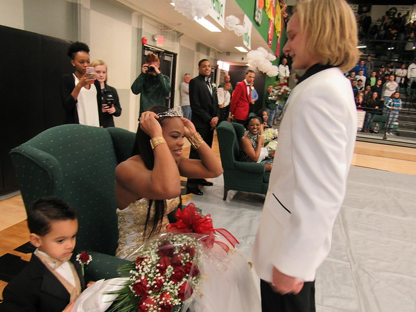 Staff photo by Cathy Spaulding<br /> Muskogee High School basketball homecoming queen Trena Mims adjusts her crown while escort Ross Ladd watches. Crown Bearer Kayzen McClain-Mims, 3, looks on.