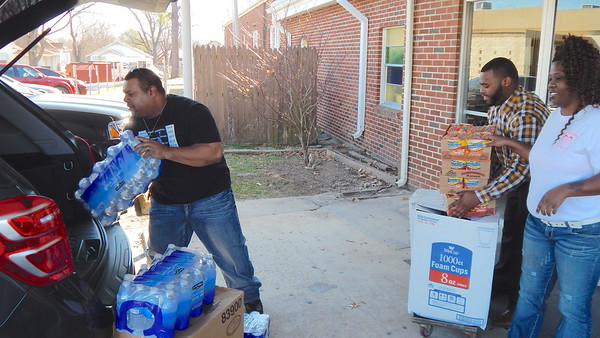 Staff photo by Mark Hughes<br /> Marcus Loggins, left, and Greg Mims load bottled water and ramen noodles into Loggins' SUV as Stacey Gandy looks on. Three child care facilities joined Latarsha Loggins' request to hold a food drive to fill the pantry at Antioch's Church of Muskogee. The donated food came from Wilkerson's Child Care. Mims is a teacher at Wilserson's and Gandy is an office assistant.