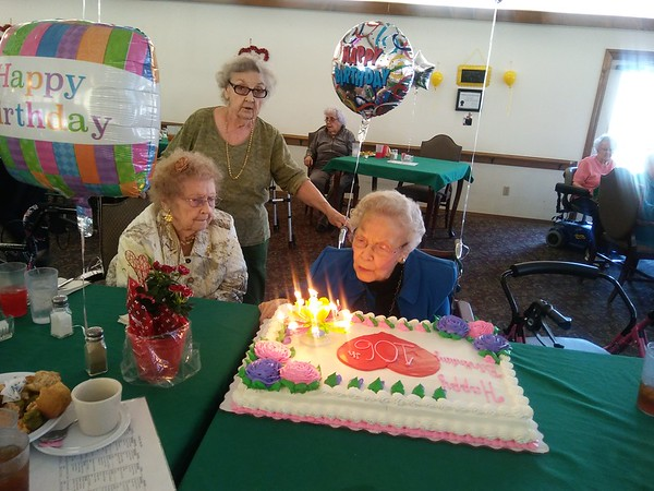 Special photo by Wendy Burton<br /> Pearl Chilcoat, who turned 106 on Saturday, blows out the candles on her cake as friends Betty Jean Winters, left, and Jean Moore watch. Chilcoat says her longevity is thanks to a positive attitude and a productive life.