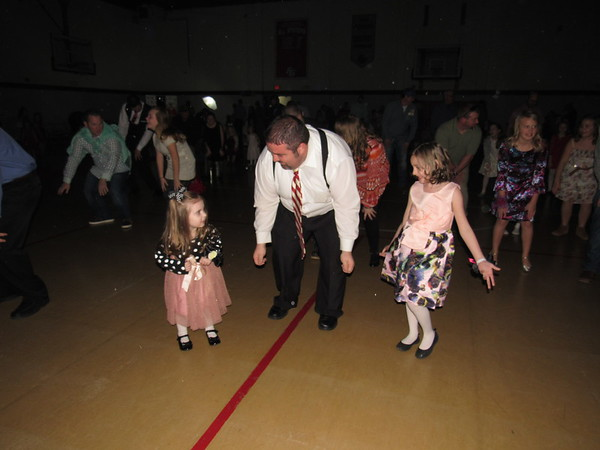 """Staff photo by Cathy Spaulding<br /> Justin Kinman gets into a """"Cha Cha Slide"""" with his 4-year-old daughter Lili, left, and his 7-year-old daughter Emma. The three slid, cha-cha'ed and Chicken Danced at the American Legion Father Daughter Dance."""