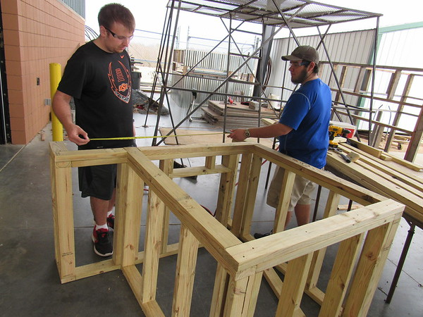 Staff photo by Cathy Spaulding<br /> Muskogee High School senior Jacob Humphrey, left, measures a scale model house frame while classmate Chris Spinks holds the tape measure. The two attend an MHS class on home construction.