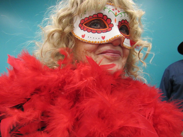 """Staff photo by Cathy Spaulding<br /> Lacy Page dons floozy-like feathers for her role in the """"Murder at the Mardi Gras"""" mystery. Muskogee Public Library will present the mystery Saturday for a matinee and a dinner."""