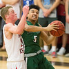 Special photo by Von Castor<br /> Muskogee's Keith Clemmons is fouled by Bishop Kelley's Ryan Gendron as he drives in the lane Friday night at Bishop Kelley in Tulsa.