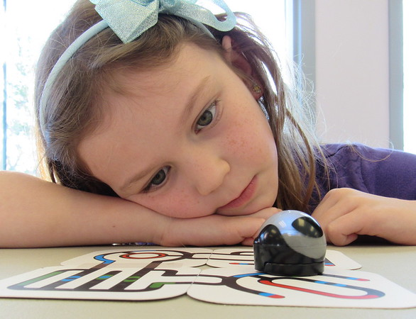 Staff photo by Cathy Spaulding<br /> Rylee Reese, 6, watches her Ozobot make its way around a colored path. Rylee learned how to program the toy robot during an after-school event at Q.B. Boydstun Library.