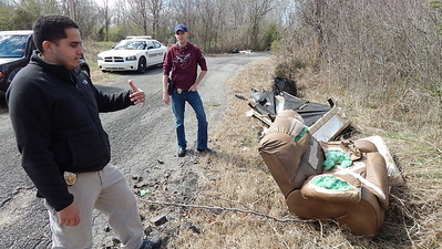 Staff photo by Mark Hughes Officer Joshua Garza talks about illegal dumpers adding furniture, household items, tires and trash along Lincoln Street between 10th and 12th streets. Officer Brandon Garner, Garza's partner, is talking to city planning officials about adding cameras to the major illegal dump sites to help catch illegal dumpers.