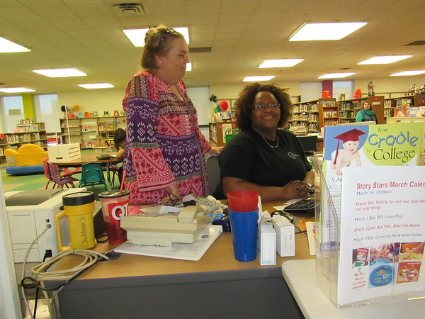 Staff photo by Cathy Spaulding<br /> Muskogee Public Library youth services director Rachelle Horney, left, visits with library assistant Shannon Brown. Brown helped Horney get acquainted with Muskogee when she moved to town.