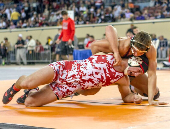 Special photo by Samuel Perry<br /> Wagoner's Malcolm Rodriguez, looks to gain an advantage atop Fort Gibson's Justin Cates in the Class 4A 182-pound championship match Saturday at State Fair Arena. Rodriguez won 8-4, taking the weight class his brother won last year.