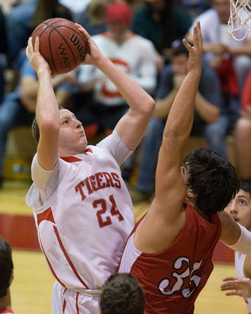 Phoenix special photo by Von Castor<br /> Fort Gibson's Kyle Dortch gets a shot off over Hilldale's Blake Thompson during Tuesday's game at Harrison Field House. The Tigers won 60-28.