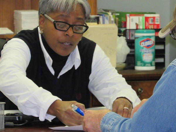 Staff phot by Cathy Spaulding<br /> Insurance company owner Traci McGee helps a customer with paperwork. McGee said she learned about customer service from Muskogee's African-American business leaders.
