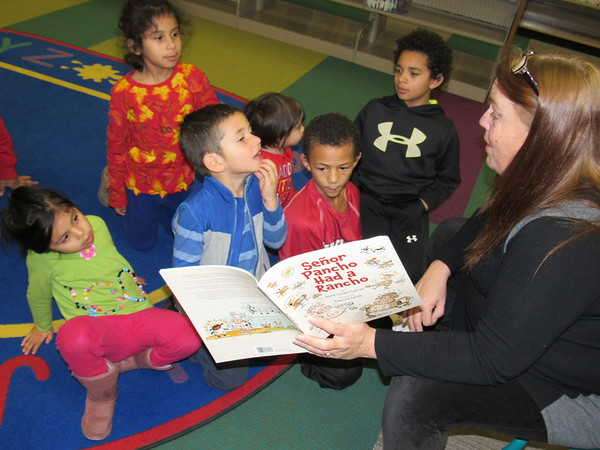 Staff photo by Cathy Spaulding<br /> Muskogee Public Library head of youth services Rachel Horney reads a Spanish version of Old McDonald to children, from left, Bateli Santos, Gila Santos, Ray Santos, Malka Santos, Armoni Stuart and Malakhiaha Stuart. The library has a bilingual story time at 6 p.m. Thursday.