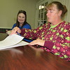 Staff photo by Cathy Spaulding<br /> Muskogee Habitat for Humanity President Amanda South, left, watches Barbara Stout inspect closing papers on Kent's house. Habitat helps Kent afford the house by offering a 0 percent interest mortgage.
