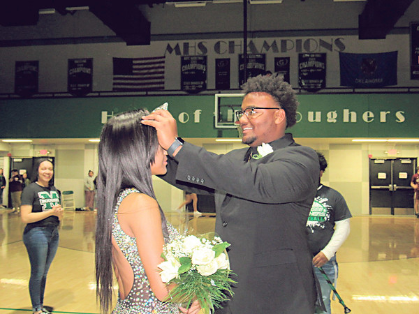 CATHY SPAULDING/Muskogee Phoenix<br /> Muskogee High School Spring Homecoming king Kaleb Biglow crowns D'Asia Brown as MHS Spring Homecoming queen during Friday night festivities.