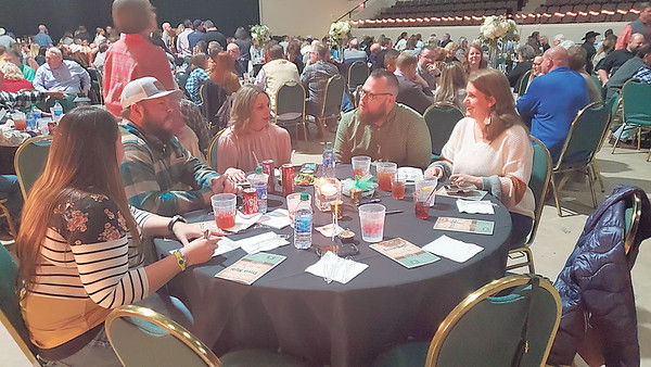 CHESLEY OXENDINE/Muskogee Phoenix<br /> Attendees at the Education Foundation of Muskogee's Trivia Night discuss an answer to a question about barbecue.