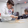 Staff photo by Mike Elswick<br /> Eden Perry, left, and Levi Perry work on an exercise on basic engineering and construction principles while their father, Robert Perry, center looks on. Jason Gonzales, technical specialist with the Muskogee Public Library, said parents wanting to connect with their youngsters while instilling STEM principles have a variety of resources available, including logging onto the Pinterest site and doing a search for STEM topics.