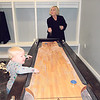 Marybeth Flusche coaxes a moving puck along a shuffleboard table while 2-year-old Van Jones watches. The table is in the groom's suite at the Eight Ten Ranch & Cattle Co.