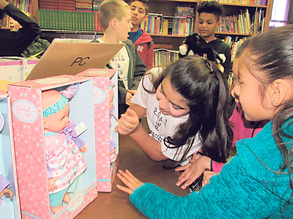 Whittier Elementary students, from left, Keira Core, Yazlyn Mata and Yesenia Perales study lifelike baby dolls they are helping to collect for patients in memory care.
