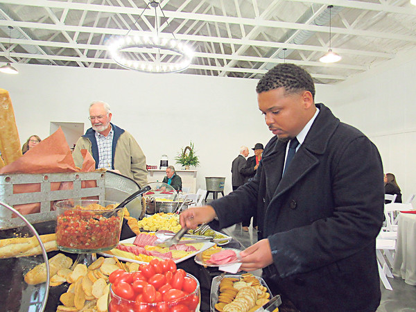CATHY SPAULDING/Muskogee Phoenix<br /> Real estate agent Omar Givens serves himself sliced meats and cheese during an open house Thursday at the Eight Ten Ranch & Cattle Co. Dozens attended the new event venue at 800 N. Country Club Road. Muskogee Tourism helped host the open house. The venue will feature 3,750 square feet of space indoor and outdoor space, bridal and groom suites.