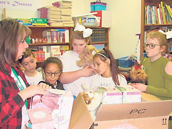 CATHY SPAULDING/Muskogee Phoenix<br /> Whittier Elementary teacher Nelita Cash fills donation boxes with students, from second left, Nicolai Whitmire, Jada Robinson, Madison Phillips, Maleah Zinn and Addyson Starkey. The students are collecting realistic baby, cat and dog dolls for patients in memory care.