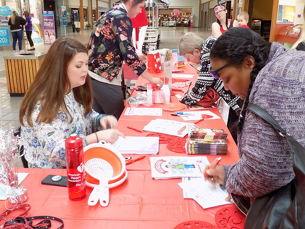 Staff photo by Mike Elswick<br /> Bailey Robinson, with the American Heart Association, left, visits with Michelle Carter Brown, right, of Oktaha during the Go Red for Women Heart Walk at Arrowhead Mall Friday.