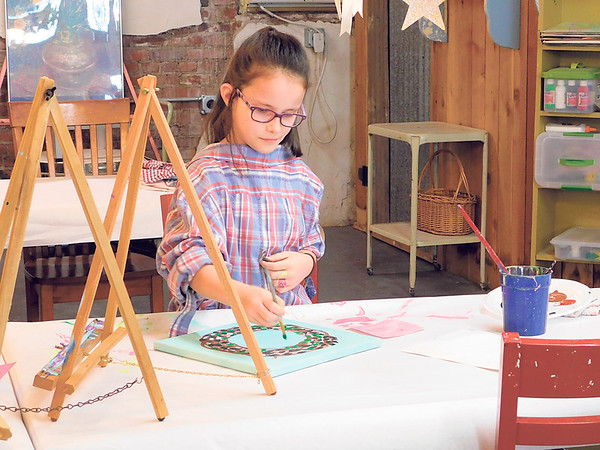 KENTON BROOKS/Muskogee Phoenix<br /> Addison Smith of Muskogee paints a wreath for Valentine's Day at the Whistle While You Work studio on South Main Street on Saturday. Artists of all ages painted banners, on canvas or wood as part of a weekly event.