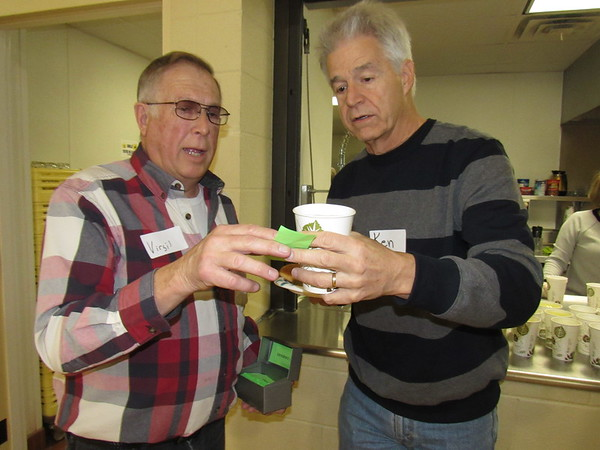 Staff photo by Cathy Spaulding<br /> Virgil Rose, left, hands a dessert ticket to Ken Beard during the Wednesday Dinner Church held at St. Paul United Methodist.