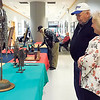 KENTON BROOKS/Muskogee Phoenix<br /> Gene Kuhlmann, left, discusses his metal sculpture with Mary Gist, the Jack C. Montgomery VA Medical Center Canteen chief, during Monday's Veterans Creative Arts Competition in the center's main lobby.