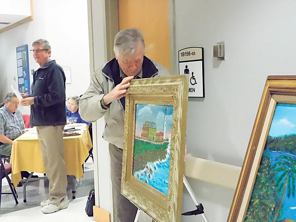 Guy Lozier of Tulsa sets up his paintings Monday at the Veterans Creative Arts Competition in the Main Lobby of the Jack C. Montgomery VA Medical Center. Lozier was one of a group of veterans who displayed their work with a chance to qualify for the national competition later this year. A U.S. Army veteran who served in Vietnam, Lozier said he's been painting for eight years.