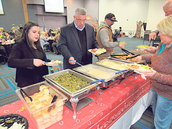 CATHY SPAULDING/Muskogee Phoenix<br /> Fort Gibson Chamber of Commerce Banquet guests — from left, Camryn Garrett, her father, incoming Chamber President Cliff Garrett, and Dawn Knupp of OG&E — help themselves to buffet items served by Charlie's Chicken.