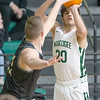 Muskogee's Peyton Clark, right, shoots a 3-point shot over Broken Arrow's Caleb Stika Tuesday night at Muskogee. The Roughers lost in overtime 59-55.