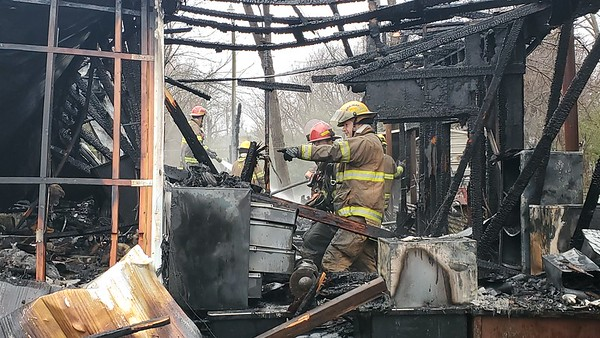 CHESLEY OXENDINE/Muskogee Phoenix<br /> Firefighters examine the ruins of a mobile home destroyed by fire Wednesday morning on Eufaula Avenue, leaving Robert Sylvie and his wife only time enough to gather their pets before escaping. The fire began at approximately 11 a.m. by a wood stove that ignited one wall of the mobile home, which quickly went up in flames, said Muskogee Fire Department Assistant Chief Gordon Lee. By the time firefighters got the fire under control, the home was destroyed. No one was injured. The Red Cross was called to help the Sylvies.