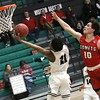 Phoenix special photo by John Hasler<br /> Muskogee's Xavier Brown lays it in for two in front of Bishop Kelley's Stephen Collins during Tuesday's game at Ron Milam Gymnasium. The Roughers won 64-56.