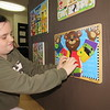 "CATHY SPAULDING/Muskogee Phoenix<br /> Gracie Holland zips a multi-activity ""jacket"" in her Hilldale Elementary classroom. Her teacher, Suzanne Murray, used a Hilldale Education Foundation grant for a Sensory Wall in her special education classroom."