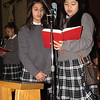 Staff photo by Cathy Spaulding<br /> St. Joseph Catholic School students Elia Sandoval, left, and Ivy  Nguyen share a hymnal during an ecumenical service for the start of Lent, held on Ash Wednesday at St. Joseph Catholic Church.