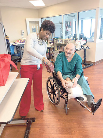 CHESLEY OXENDINE/Muskogee Phoenix <br /> Shantel McJunkins provides a gift bag to Armando Ordanza during the National Salute to Veteran Patients event at Jack C. Montgomery VA Medical Center on Thursday afternoon.