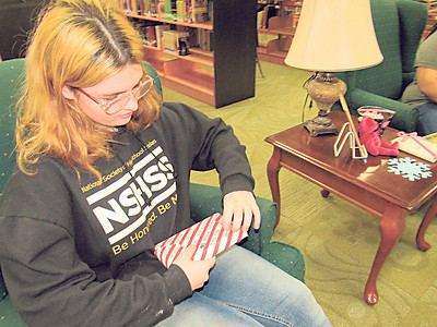 """CATHY SPAULDING/Muskogee Phoenix  Gabriel Sigle unwraps a book she got through the Muskogee High School library promotion """"Blind Date with a Book."""""""