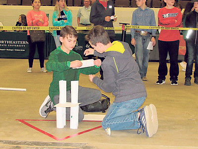 CATHY SPAULDING/Muskogee Phoenix Alice Robertson Junior High student Tucker Perkins, left, holds paper while teammate Jace Speir tapes it together during the Paper Tower Building preliminary competition Thursday during the Math and Engineering Competition.