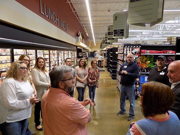 Staff photo by Mike Elswick<br /> Kevin Hadley, Harps Food Stores meat specialist, foreground, discusses the expanded meat market the new location will have when it opens Wednesday. A butcher will be on hand daily to provide fresh cuts and custom orders, he said.