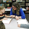 """KENTON BROOKS/Muskogee Phoenix<br /> Fourth-grader Jayda Henson, left, shares a laugh with Library Assistant Abigail """"Abby"""" Jackson at Central Intermediate School in Wagoner during Jackson's lessons about using the encyclopedia. Jackson wanted to improve the students' low scores in resource testing and acquired encyclopedias for the students to use in their work."""