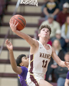 VON CASTOR/Special to the Phoenix Warner's Jack Van Daley shoots from under the basket as he gets past a Sallisaw Central defender Saturday night at Warner. The Eagles captured the Class 2A Area II district title with a 75-61 win.