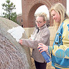 CATHY SPAULDING/Muskogee Phoenix<br /> Oktaha FFA members Georgia Perry, left, and Karley Fewel decorate a hay bale with cotton, representing a sheep at the 1200 block of West Okmulgee Avenue.