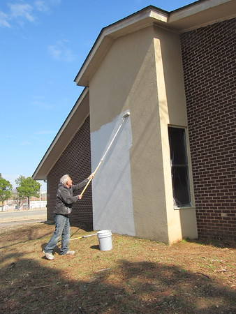 CATHY SPAULDING/Muskogee Phoenix<br /> Tim Stewart reaches his primer roller high up the exterior of the former Temple Beth Ahaba on South Seventh Street while working Tuesday. Harmony House owner Mandy Scott said she bought the property, next to the restaurant, in January. She said she plans to convert the building into Harmony Hall, a venue for parties, cake decorating classes and other events. She said the building has a kitchen as well as a stage. She said she plans the venue to be open by June.