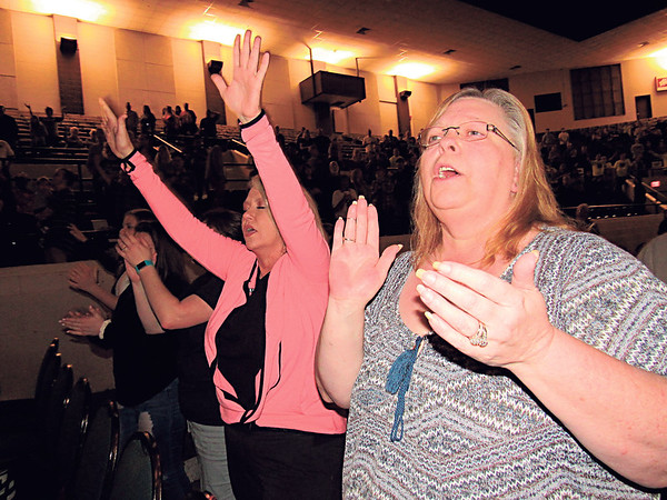 Staff photo by Cathy Spaulding<br /> Worshippers Tracy Griffin, left, and Gayle Farrow, raise their hands and clap in praise during One Blood Revival's opening songs. The revival concludes tonight.