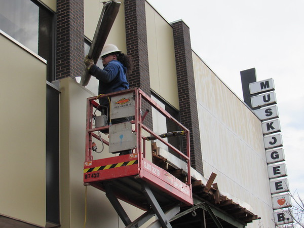 CATHY SPAULDING/Muskogee Phoenix<br /> A worker pulls metal trim from Muskogee Public Schools' BEST Center's (Board of Education Service and Technology Center) facade on Tuesday. Muskogee Public Schools is remodeling the interior and exterior of the BEST Center, formerly First National Bank, at the corner of Broadway and Second Street.