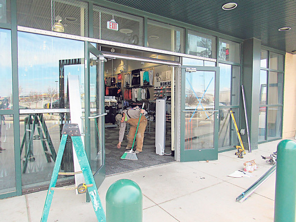 CATHY SPAULDING/Muskogee Phoenix Lloyd Hopkins of Dickmann Glass sweeps the entrance of Hibbett Sports after installing glass doors Wednesday. Construction is ongoing at several stores at Three Rivers Plaza on West Shawnee Bypass.