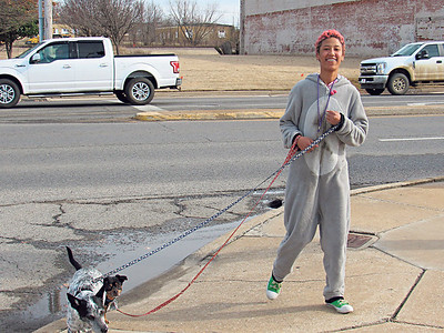 CATHY SPAULDING/Muskogee Phoenix Blanche Jacks guides her dogs Oreo, left, and Buster along a Main Street sidewalk on Wednesday afternoon. Pleasant, cool weather is expected to continue until Saturday, when it warm to the low 60s.