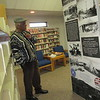 """CATHY SPAULDING/Muskogee Phoenix<br /> Retired teacher James Johnson studies a traveling exhibit, """"Tulsa Race Massacre and Spirit of Greenwood,"""" Thursday at Warner Public Library. The exhibit will be at Haskell's Rieger Memorial Library through the end of February."""