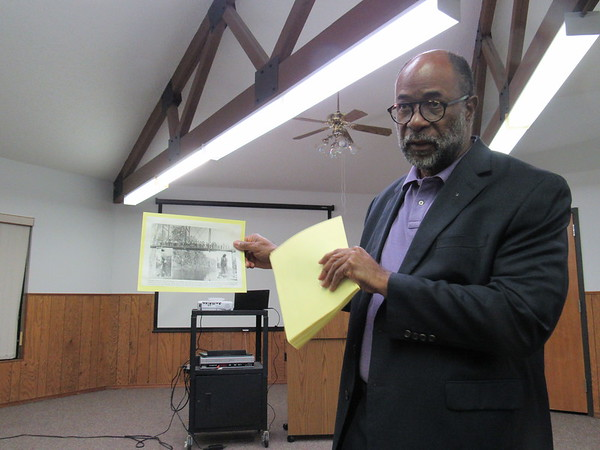 """CATHY SPAULDING/Muskogee Phoenix<br /> Historian Jimmie White shows a picture of two people being lynched in Okemah in the early 20th Century. He said lynching was a way to """"keep black people in line."""" He spoke about how such attitudes were a backdrop to the 1921 Tulsa Race Massacre."""