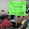 Staff photo by Cathy Spaulding<br />   Pershing Elementary first-grade teacher Jacqueline Bennett holds up a sign expressing her concern for education funding. Bennett joined dozens of other teachers at the Muskogee Board of Education meeting on Tuesday.