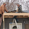 CATHY SPAULDING/Muskogee Phoenix<br /> Mike Connelly, left, watches Barney Connelly set a beam for a front porch eave Thursday. Connelly Brothers Construction of Vian is contracting with the United Keetowah Band of Cherokees on a housing program. They built a handicapped access ramp and did the porch improvements for a Muskogee resident.