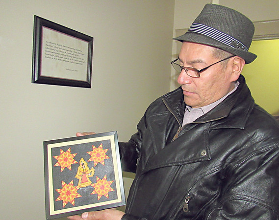 CATHY SPAULDING/Muskogee Phoenix<br /> Bacone College Art Director Gerald Cournoyer shows a work by Martin Redbear to be sold at a March raffle auction benefiting Bacone's art program and collection.